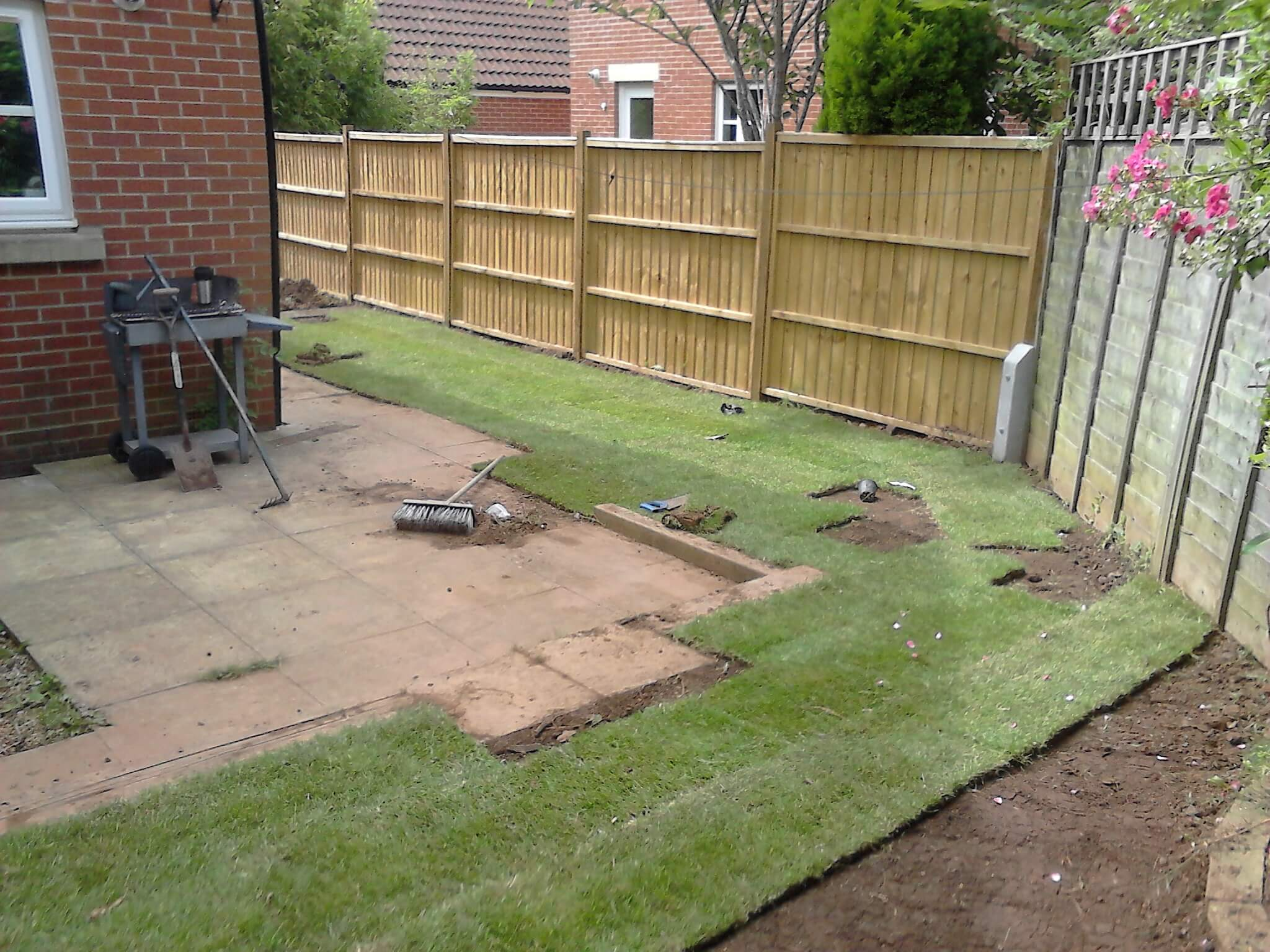 Landscape image of a Bristol garden with fence being turfed by Bristol gardener, Bark and Gardens